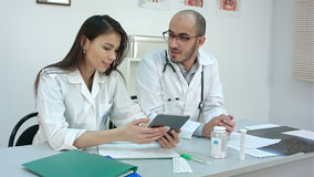 Pretty young nurse showing something on the tablet to her male colleague stock video footage