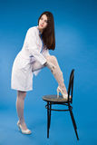 A pretty young nurse straightens stockings Royalty Free Stock Photography