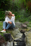 Pretty young pensive girl sitting by some rocks. In a forest Stock Photo