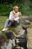 Pretty young pensive girl sitting by some rocks. In a forest Royalty Free Stock Images