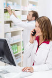 Pretty young pharmacist chatting on the phone Royalty Free Stock Photo
