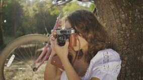Pretty young photographer with curly hair sitting under the tree taking photo using old camera in the garden or park. Attractive young photographer with curly stock video footage