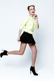 Pretty young playful girl dressed in green pullover and black skirt. Royalty Free Stock Photography