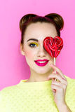 Pretty young playful girl holding heart-shaped lollipop Stock Photos