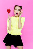 Pretty young playful girl holding heart-shaped lollipop Stock Photography