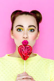 Pretty young playful girl holding heart-shaped lollipop Stock Photo