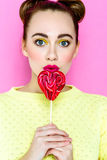 Pretty young playful girl holding heart-shaped lollipop Royalty Free Stock Images