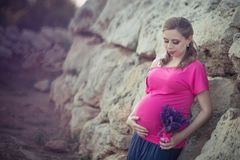 Pretty young pregnant lady woman with huge beautifull green eyes and pout red lips wearing dark pink dress with blue skirt holding. Hands on her tummy awaiting stock images