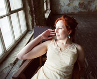 Pretty young red hair woman in old -fashioned style room sitting smiling at window and typing machine, art vintage Royalty Free Stock Photo