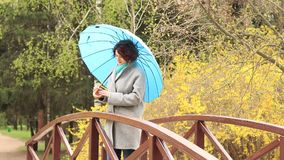 Pretty young red head woman with the blue umbrella. On the bridge in spring park. Green trees and forsythia blossoms background stock footage