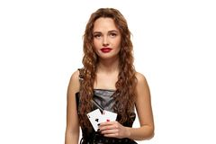 Pretty young redhead or brown-haired woman holding pair of aces in black leather dress isolated on white. Pretty young redhead or brown-haired woman smiling stock image