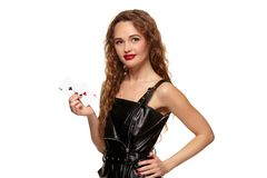 Pretty young redhead or brown-haired woman holding pair of aces in black leather dress isolated on white. Pretty young redhead or brown-haired woman smiling stock photos
