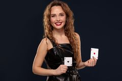 Emotional pretty young redhead woman holding pair of aces in black leather dress on black background. Pretty young redhead or brown-haired woman smiling, holding stock image