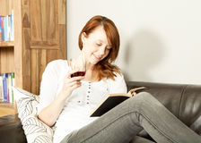 Pretty young redhead woman reading a book Royalty Free Stock Photography