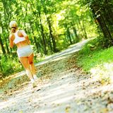 Pretty Young Runner. Pretty young girl runner in the forest royalty free stock photography