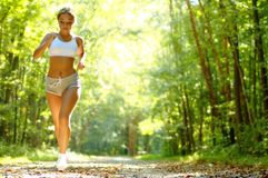 Pretty Young Runner. Pretty young girl runner in the forest royalty free stock photo
