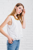 Pretty young sexy fashion sensual woman posing on white wall background dressed in hipster style jeans outfit,Stylish Royalty Free Stock Photos