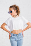 Pretty young sexy fashion woman posing on white brick wall Royalty Free Stock Photography