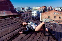 Pretty young sexy woman lying on the wooden roof Stock Photography