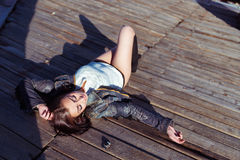 Pretty young sexy woman lying on the wooden roof Stock Image