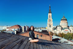 Pretty young woman sitting on the wooden roof Stock Photography