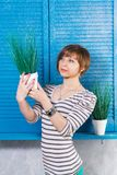 Pretty young short haired caucasian girl holding pott?d plant near blue window. Studio shot, gardening concept, copy space. royalty free stock photo