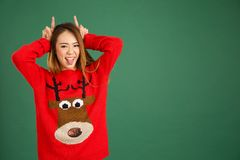 Pretty young singaporean girl wearing Christmas jumper and doing. Horns Stock Photos