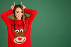 Pretty young singaporean girl wearing Christmas jumper and doing. Horns with her fingers Royalty Free Stock Photography