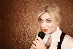 Pretty young singer or comedian with microphone Royalty Free Stock Image