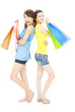 Pretty young sisters standing and holding shopping bags Stock Images