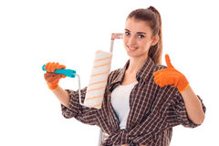 Pretty young slim builder girl makes renovations with paint roller isolated on white background Stock Image