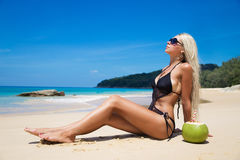 Pretty young slim woman on beach near blue clean water. Pretty young slim woman on a beach near blue clean water on white sand Stock Photo