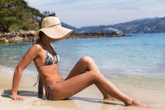 Pretty young slim woman on beach near blue clean water Stock Image