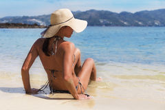 Pretty young slim woman on beach near blue clean water Stock Photos