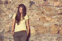 Pretty young slim woman with yellow t-shirt and brown pants stock images