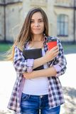 Pretty young smiling cheerful female student in casual clothes h stock photo