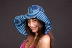 Pretty young smiling girl in hat on dark Stock Images
