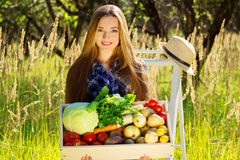 Pretty and young smiling girl keeping wooden box full of vegetables. Summer harvest. royalty free stock photos