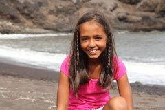 Pretty young smiling school girl sitting on beach Royalty Free Stock Photo