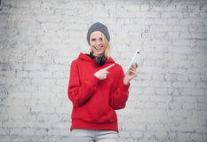 Pretty young smiling woman in red sweatshirt and grey hat with the headphones on her neck standing by the brick wall royalty free stock photo