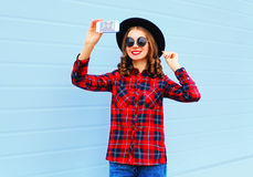 Pretty young smiling woman taking picture self portrait on smartphone in city, wearing fashion black hat red checkered shirt. Over blue background Royalty Free Stock Photos