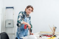 Pretty young smiling woman using cordless drill. A pretty young smiling woman using cordless drill Royalty Free Stock Photo