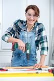 Pretty young smiling woman using cordless drill. A pretty young smiling woman using cordless drill Stock Photography