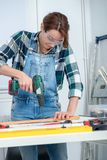 Pretty young smiling woman using cordless drill. A pretty young smiling woman using cordless drill Stock Images