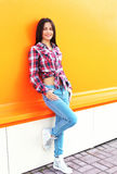 Pretty young smiling woman wearing a checkered shirt and jeans Stock Photo
