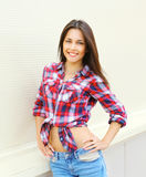 Pretty young smiling woman wearing a checkered shirt. Posing in the city Royalty Free Stock Photos
