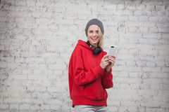 Pretty young smiling woman wearing red sweatshirt and grey hat standing by the brick wall and holding phone in her hands stock images