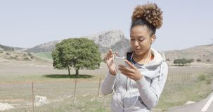 Pretty young sportive woman with phone stock footage