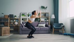 Pretty young sportswoman doing complex of physical cardio exercises at home. Doing pushups then jumping practising in light flat alone. Millennials and beauty stock video footage
