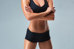 Pretty young sportswoman with a sports figure on gray background Stock Photography